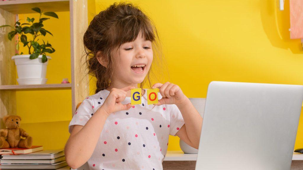 petite fille qui écris go avec des carte lettre
