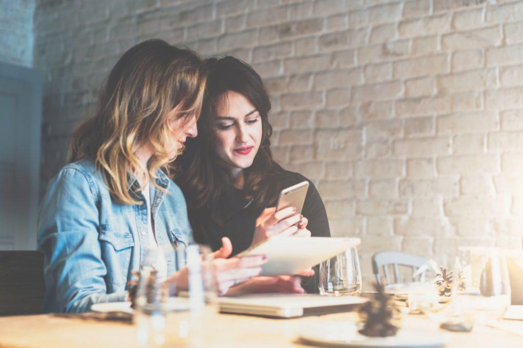amis qui souris avec un telephone et une tablette